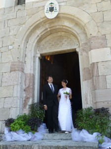 Conor and Caterina after their marriage at the Basilica Santuario dei Ss Vittore e Corona in Feltre. The floral arrangements are pots of  basil the bride's father grows in the family garden in the old town walls.
